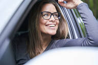 Portrait of smiling woman in a car - PNEF01888