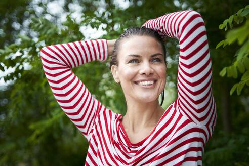 Portrait of happy woman with wet hair wearing striped top in nature - PNEF01933