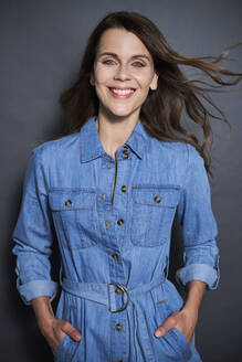 Portrait of smiling attractive woman wearing denim dress - PNEF01960