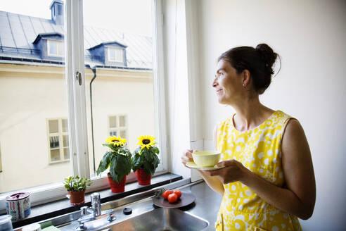Woman drinking coffee and looking through window - FOLF10342