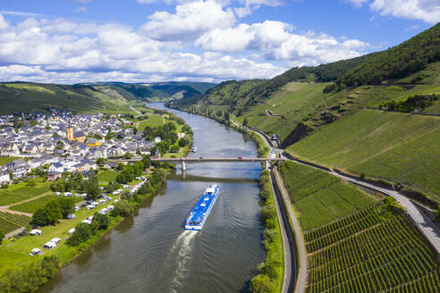 Drone shot of passenger ship on Mosel River by town against cloudy sky, Germany - RUNF02932