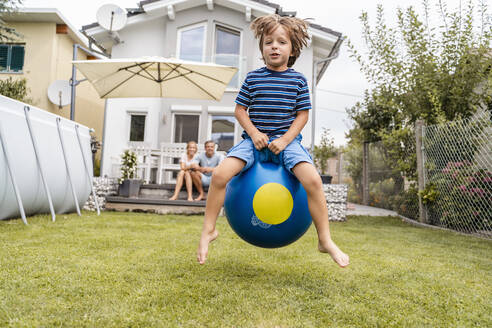 Boy bouncing with hopball in garden with parents in background - DIGF08146