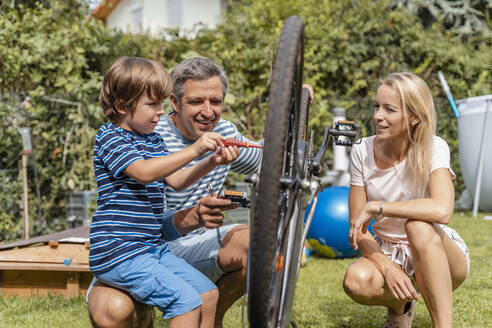 Family repairing a bicycle together in garden - DIGF08152