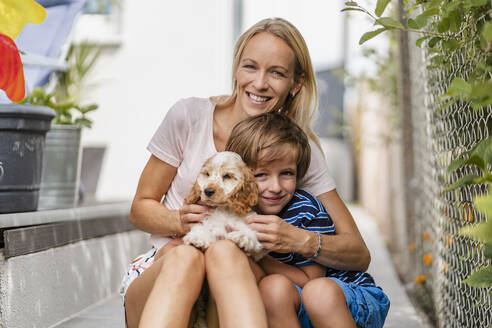 Portrait of mother snd son cuddling with cute dog puppy - DIGF08164