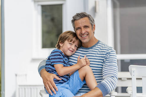 Portrait of father carrying son in garden - DIGF08170