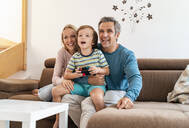 Happy parents with son playing video game on couch at home - DIGF08188