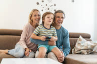 Happy parents with son playing video game on couch at home - DIGF08191