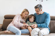 Family on couch at home with boy listening to music with headphones - DIGF08203