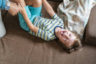 Playful father and son on couch at home - DIGF08218