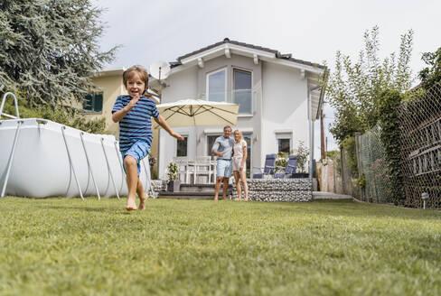 Boy running in garden with parents watching - DIGF08236