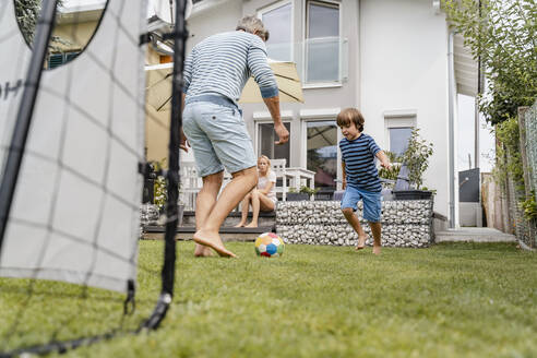 Father and son playing football in garden - DIGF08239