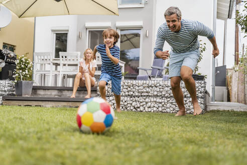 Father and son playing football in garden - DIGF08242