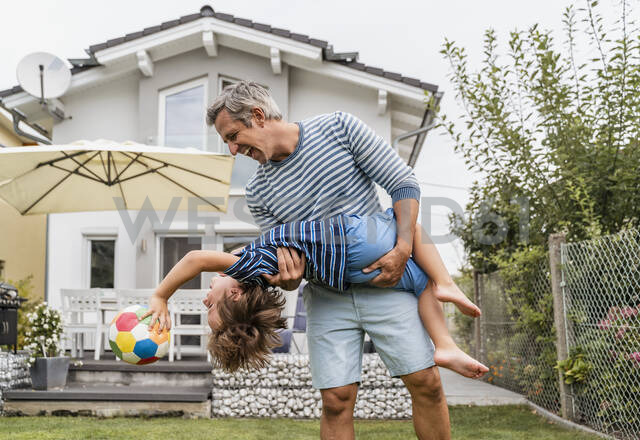 Playful father and son with football in garden - DIGF08245 - Daniel Ingold/Westend61
