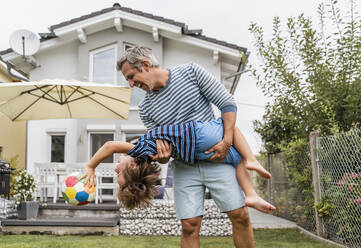 Playful father and son with football in garden - DIGF08245