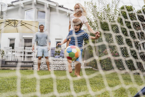 Happy family playing football in garden - DIGF08248