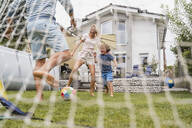 Happy family playing football in garden - DIGF08251