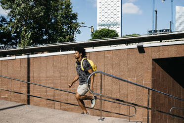 Man with yellow backpack and headphones running upstairs, Barcelona, Spain - JRFF03686
