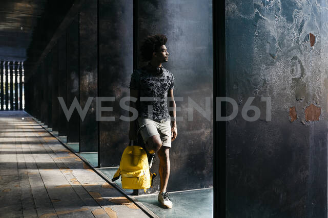 Man with yellow backpack looking at distance, Barcelona, Spain - JRFF03695 - Josep Rovirosa/Westend61