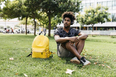 Portrait of man sitting on a meadow listening music with cordless headphones, Barcelona, Spain - JRFF03704