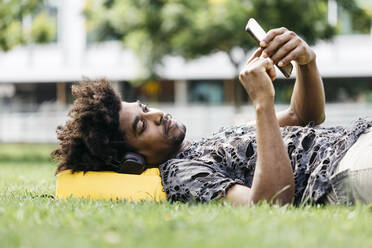 Man lying on a meadow listening music with headphones while using mobile phone, Barcelona, Spain - JRFF03707