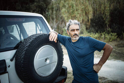Mature man standing at his off-road vehicle - OCMF00642