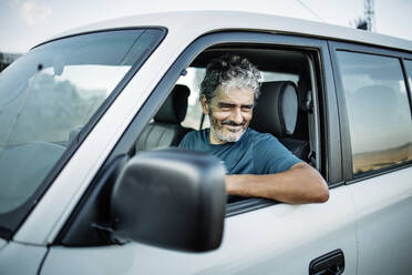 Smiling mature man sitting in his off-road vehicle - OCMF00645