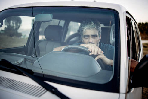 Mature man sitting in his off-road vehicle - OCMF00648