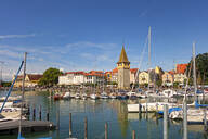 Boats moored at harbor with buildings in background against blue sky, Lindau, Germany - LHF00686