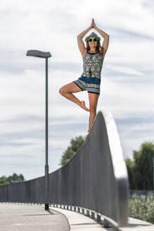 Smiling young woman balancing on a bridge railing - STSF02234