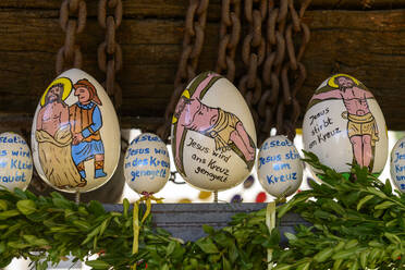 Close-up of Easter eggs with text and drawings hanging on fountain, Franconia, Germany - LB02722