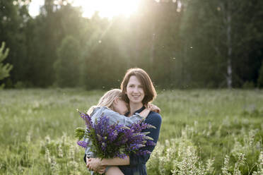 Portrait of mother and little daughter with bunch of lupines on a meadow - EYAF00474