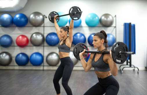 Twin sisters training with weights in gym - OCMF00652