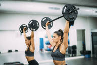 Twin sisters training with weights in gym - OCMF00655
