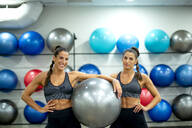 Portrait of smiling twin sisters in gym with a fitness ball - OCMF00658