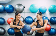Twin sisters in gym practicing with a ball - OCMF00664