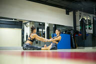 Twin sisters doing stretching exercise in gym - OCMF00670