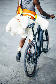 Handsome African man makes the delivery of messenger with bicycle, delivers a teddy bear. - OCMF00676