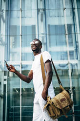 Young man with mobile phone in the city - OCMF00682