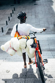 Rear view of bicycle courier delivering a teddy bear - OCMF00691
