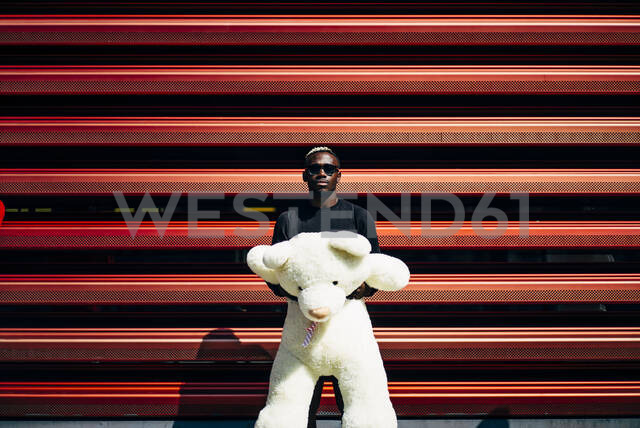 Portrait of cool young man holding huge teddy bear - OCMF00697 - Oscar Carrascosa Martinez/Westend61