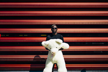 Portrait of cool young man holding huge teddy bear - OCMF00697