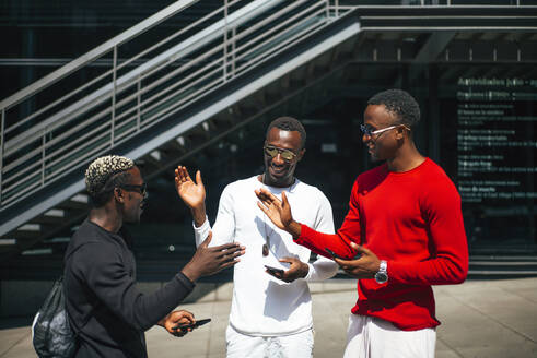 Three African men connect with each other by telephone and greet each other with hands. - OCMF00703