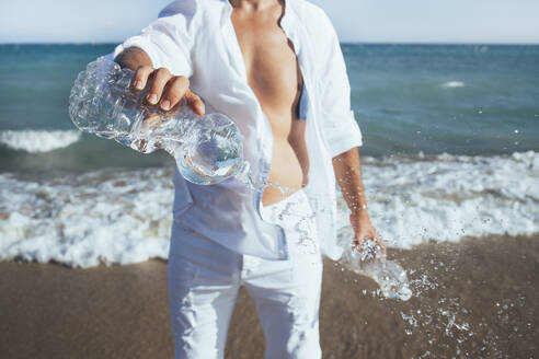 Man standing in front of seashore emptying plastic bottles, close-up - CJMF00006