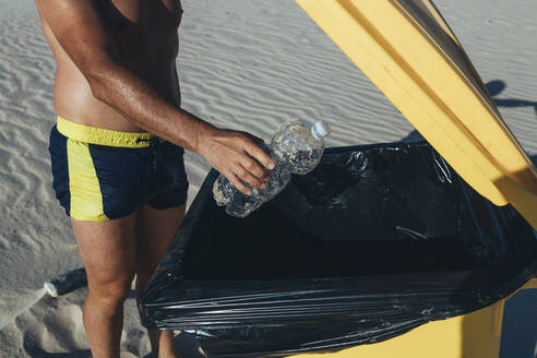 Man on the beach putting plastic bottle into waste bin, partial view - CJMF00009