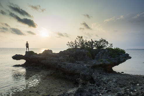 Man on a rock at seacoast in Ouvea, Loyalty Islands, New Caledonia - RUNF03053