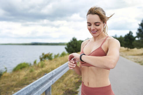 Portrait of fit woman checking smartwatch during outdoor jogging session - BSZF01390