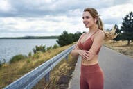 Athletic woman standing outdoors with crossed arms and looking away - BSZF01393