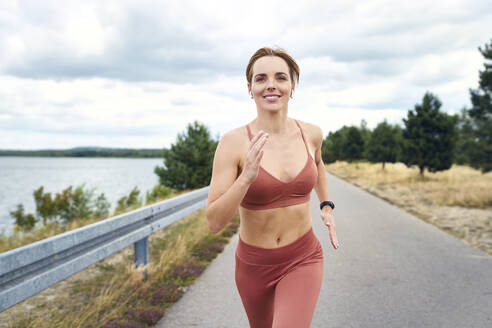 Portrait of smiling athletic woman jogging outdoors - BSZF01396