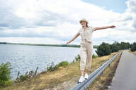 Happy woman balancing on crash barrier at the lakeside - BSZF01408