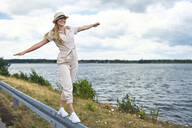 Happy woman balancing on crash barrier at the lakeside - BSZF01414